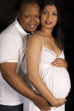 Sexy beautiful pregnant Indian woman and african male embracing in white dress smiling on black backdrop photo