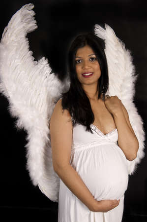 A beautiful pregnant Indian woman in white dress and angel wings smiling on black backdrop photo