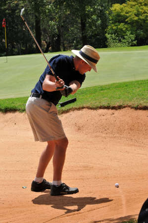young sporting adult man playing golf shot out of the sand bunker hazard onto the green with the ball visible photo