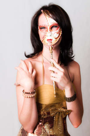 Beautiful young brunette sexy model dressed in gold with colorful red and gold venetian carnival face mask photo