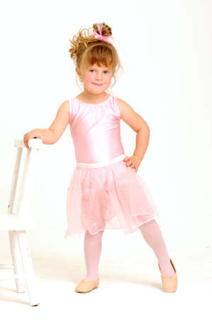 Little smiley girl wearing a pink ballet outfit is dancing holding her dress Stock Photo - 9841291