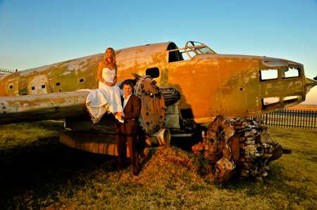 sexy young adult wedding couple standing at crashed DC3 Dakota war plane photo