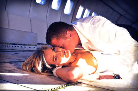 airplane girl: sexy young  adult wedding couple laying in the fuselage of airplance and kissing
