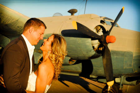 airforce: sexy young adult wedding couple standing with old war Albatross aircraft