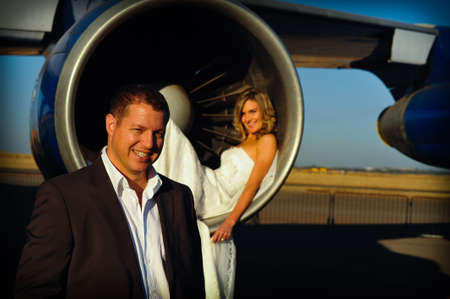 sexy young adult wedding couple laying inside the engine intake of Boeing passenger aircraft with groom infront photo