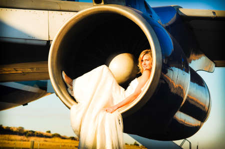 passenger aircraft: sexy young adult wedding model laying inside the engine intake of Boeing passenger aircraft Stock Photo