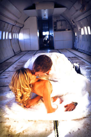 sexy young  adult wedding couple laying in the fuselage of airplance photo