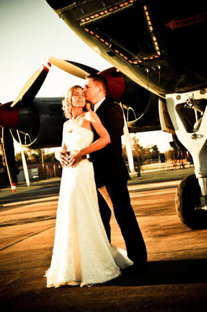 sexy young adult wedding couple standing with old war Albatross aircraft photo
