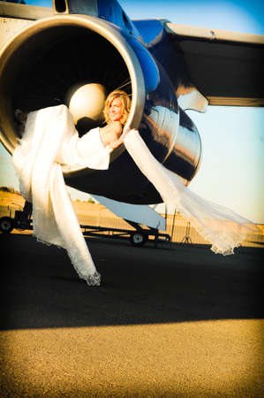 sexy young adult wedding model laying inside the engine intake of Boeing passenger aircraft photo