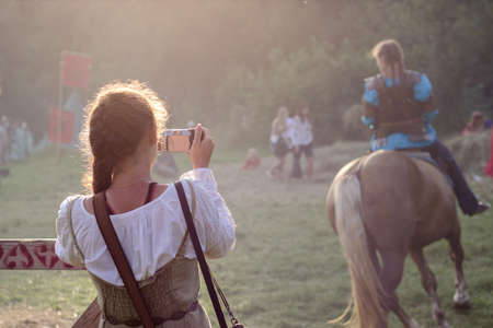 plastron: Girl wearing medieval clothes is taking a photo of a knight-girl on horseback. Urych, Ukraine - August 2: Tustan Medieval Culture Festival in Urych, Western Ukraine, on August 2, 2014