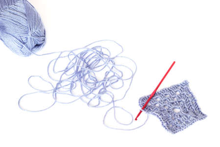 unwound: Light blue skein of acrylic thread with the unwound string, square crochet element and red hook isolated on white Stock Photo