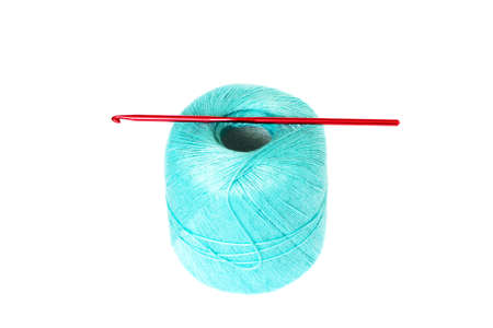 motton blue: Red crochet hook is sticked into the turquoise thread clew, isolated on white background
