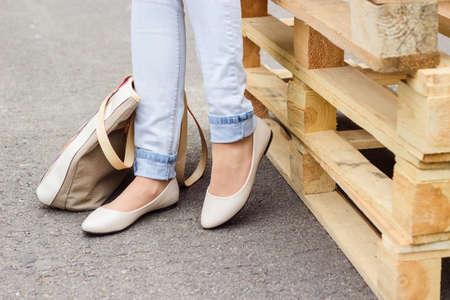 personas caminando: Piernas de la mujer en pantalones vaqueros y zapatos planos del ballet blanco con bolsa de color beige, de pie cerca de paletas de madera Foto de archivo