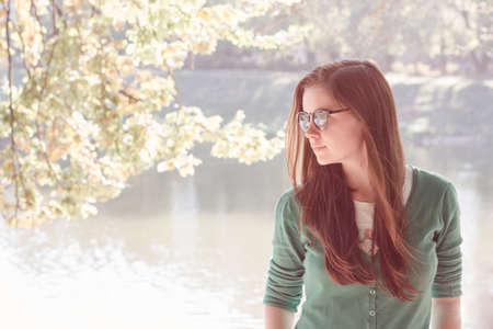 back lighting: Beautiful young woman wearing green sweater and sun glasses, standing near the pond in the park. Summer fashion concept. Back lighting and pastel toning, space for your text
