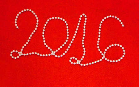 2016 New Year inscription made of white beaded necklace on vibrant red felt background