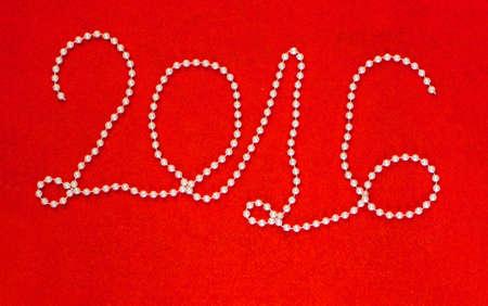 2016 年碑文製鮮やかな赤のフェルトの背景に白のビーズのネックレス 写真素材