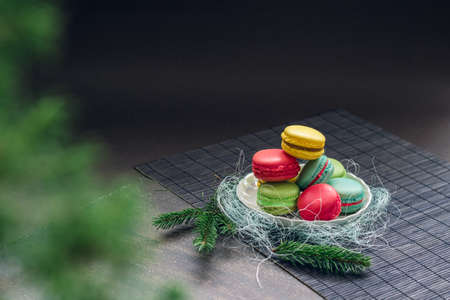 small plate: Winter still life with traditional French macaroons on the small plate and fir tree branches. Space for your text on the top of the image