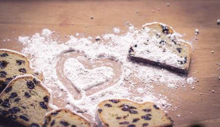 sugar powder: Stollen, traditional German Christmas yeast cake with raisins on wooden table, heart drawn on sugar powder