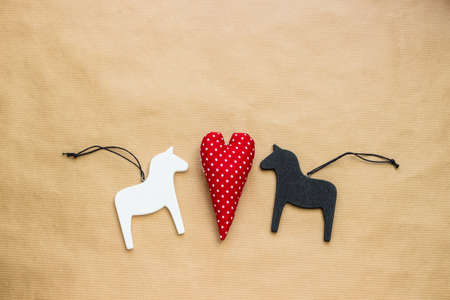 Black and white wooden toy horses and red polka dot soft heart shape toy between them on craft paper background Stock Photo