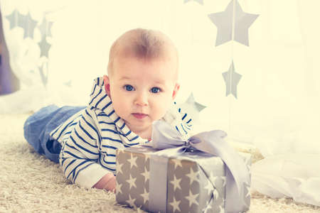 1st: Portrait of a cute baby boy with big blue eyes wearing jeans and striped hoodie sweater lying in front of his present in wrapped box with ribbon. Birthday or Christmas presents concept Stock Photo