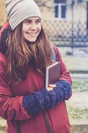 book jacket: Beautiful hipster girl with long brown hair, holding book in her hands in winter clothes outdoor (wearing grey hat, red jacket, black knitted scarf and blue mittens)