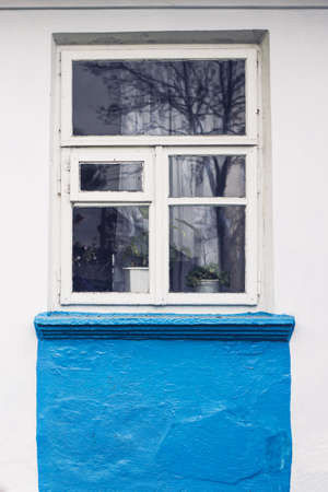 whitewash: White wooden frame window in old Ukrainian village house with whitewash wall partly pained in blue
