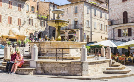 figuring: ASSISI, ITALY - SEPTEMBER 4, 2016: Couple of tourists sitting at the historic fountain figuring three lions and medieval buildings in the background on Piazza del Comune the main square of Assisi, Umbria, Italy Editorial