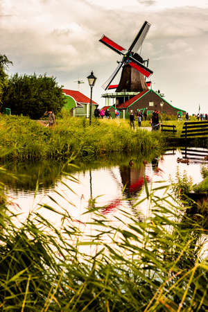 ZAANSE SCHANS, NETHERLANDS - AUGUST 24, 2014: Nature and windmills in Zaanse Schans, North Holland, Netherlands. Popular tourist destination in Netherlands