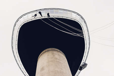 euromast: ROTTERDAM, THE NETHERLANDS - AUGUST 23, 2014: Three people abseiling from the Euromast tower, Rotterdam, the Netherlands