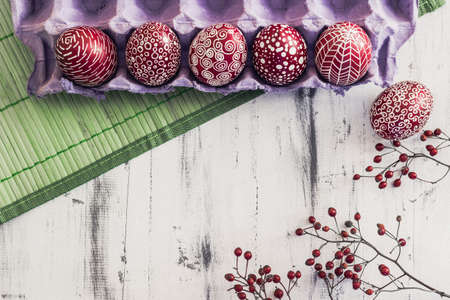 polish lithuanian: Decorated Easter eggs using a traditional in Eastern Europe wax-resist method and modern patterns. Still life with Pysanka, dry plants and lace on whitewashed wooden background, top view, copy space