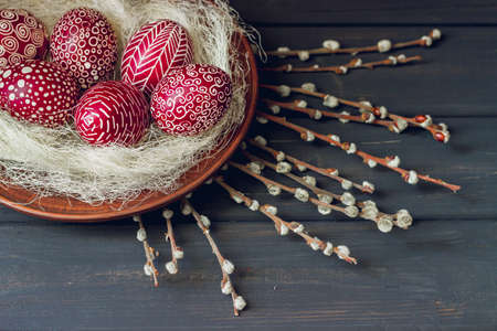 Still life with Pysanka, decorated Easter eggs, dry willow branches on black wooden background, top view, copy space Banco de Imagens