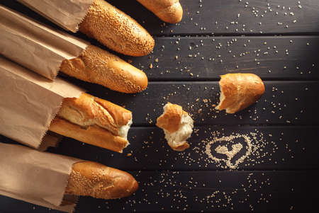 French baguettes in paper bags on black wooden background, heart drawn on sesame seeds