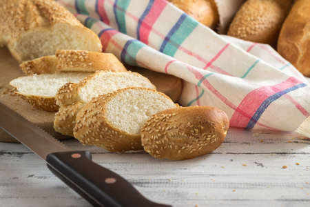 French baguette with sesame seed cut with a knife on cutting board on bright wooden background