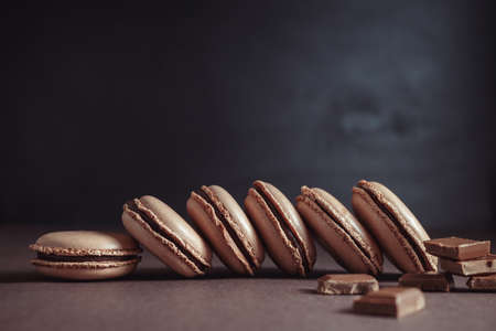 Row of Chocolate pastel brown Macarons or Macaroons over dark background Stock Photo