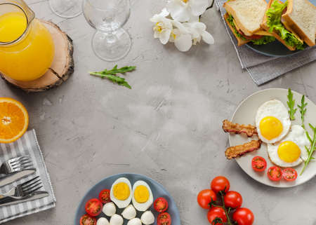 Breakfast table with fried eggs, bacon, cherry tomatoes, sanwiches