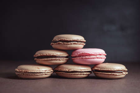 Pyramid of Chocolate Macaroons over dark background, one of them is different, Raspberry pink pastel colored Macaron. Unique, initiative, dissent, think different, business success concept, stand out from the crowd concepts