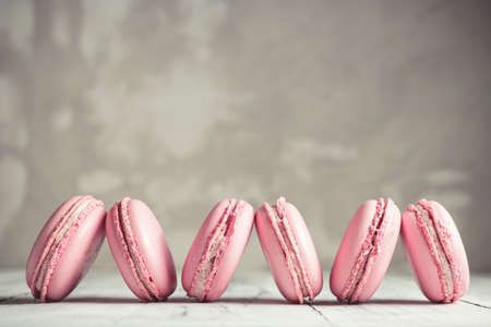 Row of Raspberry pastel pink Macarons or Macaroons over concrete stone background Stock Photo