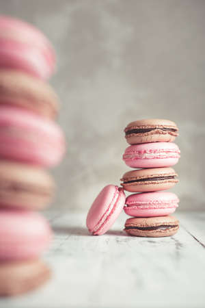 Stack of Raspberry and Chocolate pastel colored Macarons or Macaroons over concrete stone background