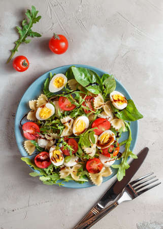 Farfalle bow tie pasta salad with quail eggs, cherry tomatoes, rucola, mozzarella and basil, dressed with balsamic sauce over grey concrete background Stock Photo