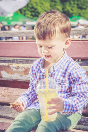 frowned: Two years old boy frowned when he tasted a bitter lemon seed while drinking lemonade. Poor quality food, street food concept Stock Photo