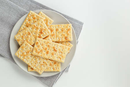 Closeup of a snack plate. Stack of crackers on grey plate and grey napkin over white background