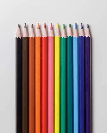 Line of 12 colour pencils on grey background. Top view