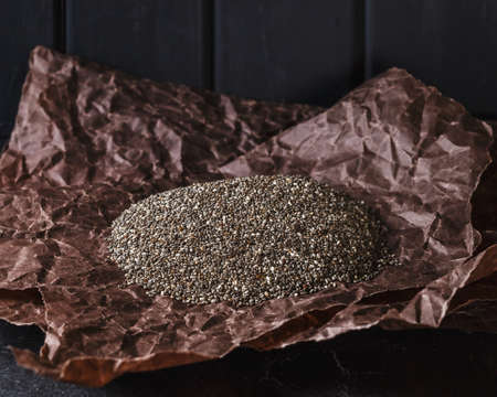 parer: Heap of healthy organic chia seeds on brown crumpled parer Stock Photo