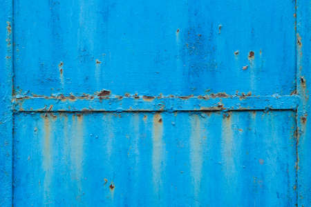 Old metal door with handle background. Rust surface covered with blue paint