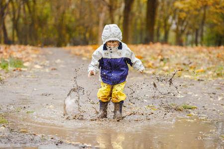 Heureux garçon de deux ans sautant sur des flaques boueuses dans des bottes en caoutchouc Banque d'images - 89452952