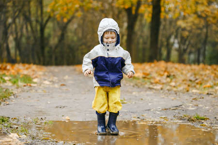 Happy two years old boy jumping on muddy puddles in rubber boots
