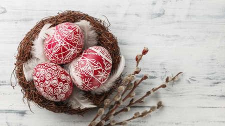 Pysanky、巣に飾られたイースターエッグ、白い木製の背景に猫の柳の枝や羽、ワイドフォーマット、トップビュー、コピースペース