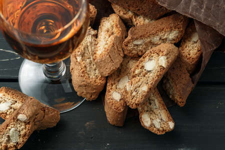 Italian cantuccini biscuits and a glass of sweet Vin Santo wine over wooden background