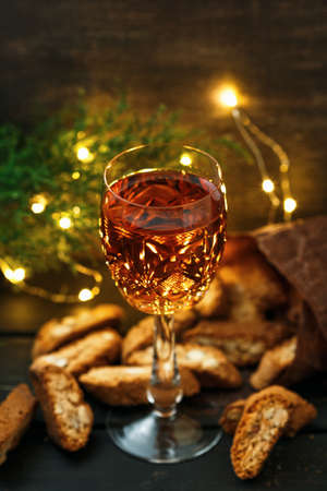 Italian cantuccini biscuits and a glass of sweet Vin Santo wine over dark wooden background and lights bokeh