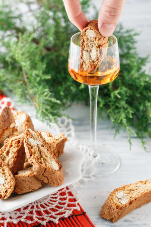 Female hand dip traditional Italian cantuccini biscuits into a glass of sweet Vin Santo wine